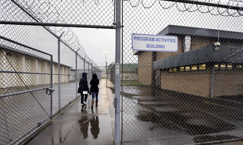 In this photo taken Thursday, Jan. 28, 2016, staff members head past razor wire-topped fences and into a building hosting a University Behind Bars program at the Monroe Correctional Complex in Monroe,