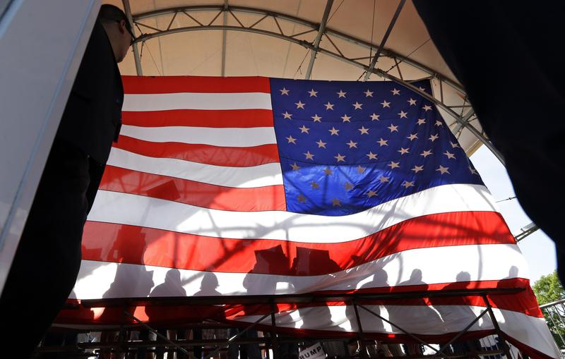 People standing behind Republican presidential candidate Donald Trump are seen in silhouette against a large American flag from backstage Saturday, May 7, 2016, in Lynden, Wash.