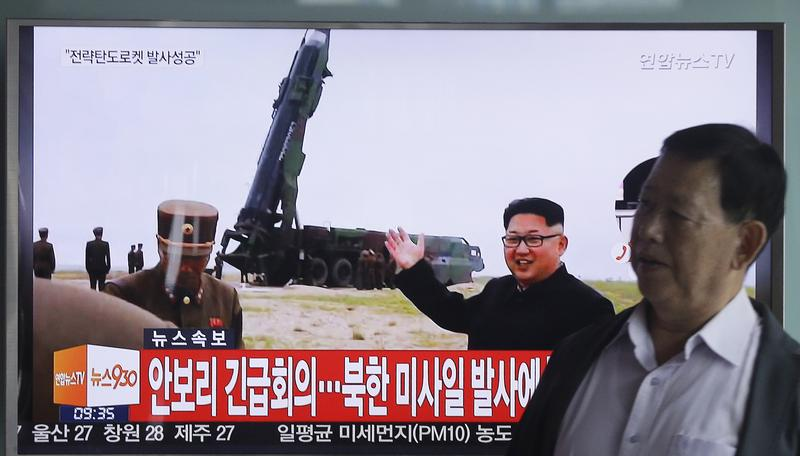 A man passes a TV showing an image of North Korean leader Kim Jong Un as he boasts of the success of a powerful new midrange ballistic missile test. June 23, 2016