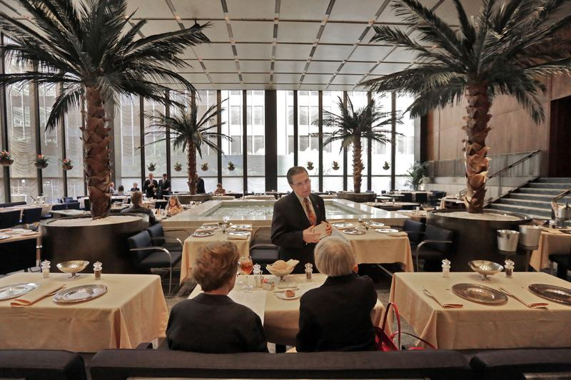 In this July 12, 2016 photo, a waiter speaks with diners in the Pool Room of The Four Seasons, in New York's landmarked Seagram building, which has housed the restaurant for 57 years.