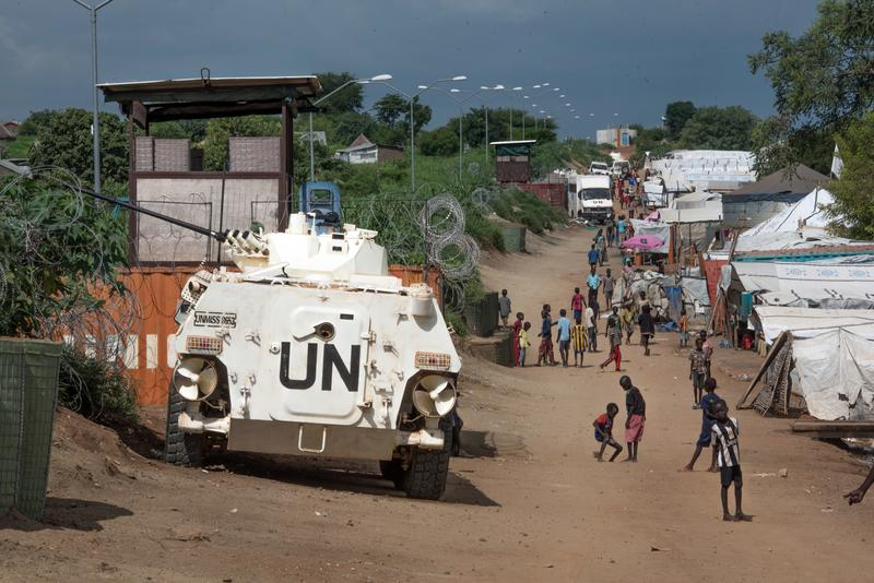 In this Monday, July 25, 2016 file photo, some of the more than 30,000 civilians sheltering in a United Nations base in South Sudan's capital Juba walk by an armored vehicle.