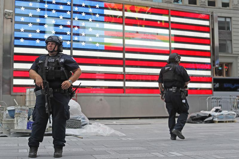 After the Chelsea blast, heavily armed police officers stand guard in the Armed Forces recruitment center island in New York's Time Square, Sunday, Sept. 18, 2016.