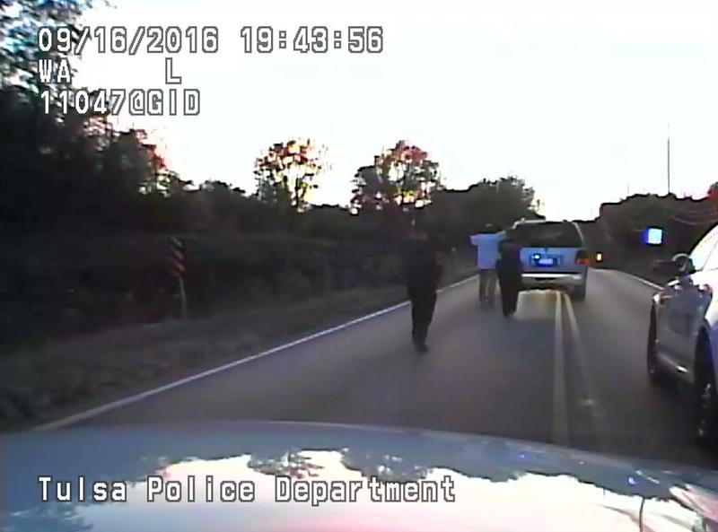 In this image made from a Friday, Sept. 16, 2016 police video, Terence Crutcher, center, is pursued by police officers as he walks to an SUV in Tulsa, Okla.
