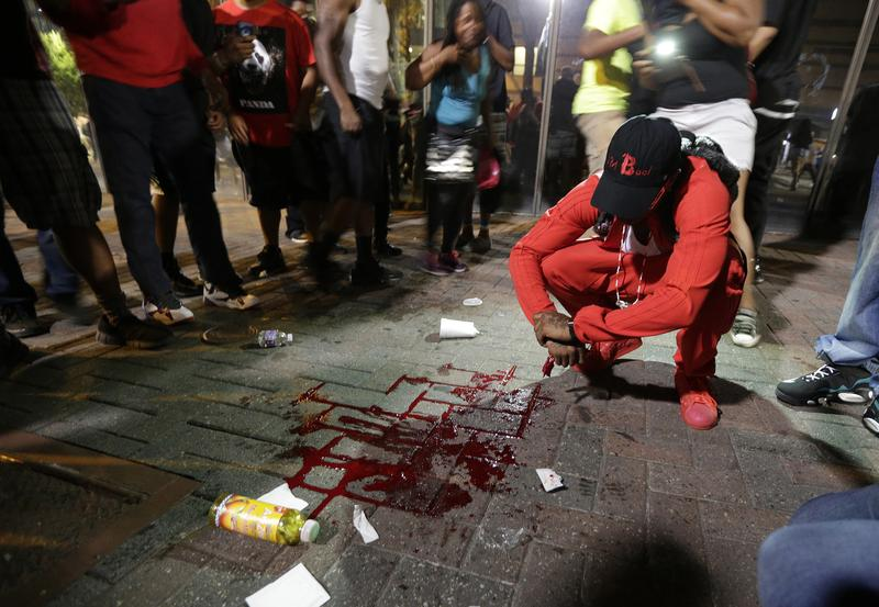 A man squats near a pool of blood after a man was injured during a protest of Tuesday's fatal police shooting of Keith Lamont Scott in Charlotte, N.C. on Wednesday, Sept. 21, 2016.