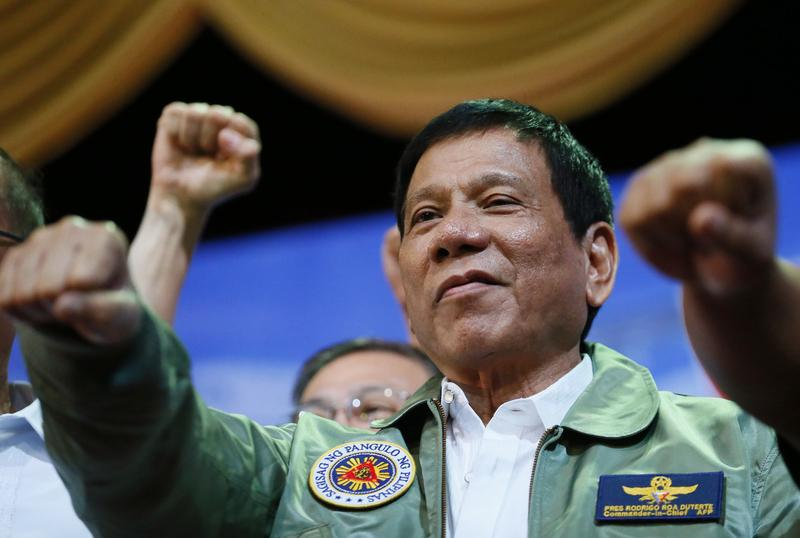 In this Tuesday, Sept. 13, 2016, file photo, Philippine President Rodrigo Duterte poses with a fist bump during the anniversary of the 250th Presidential Airlift Wing.
