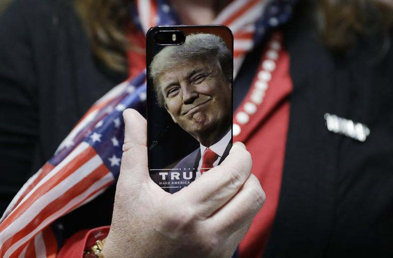 A woman holds up her cell phone before a rally with Republican presidential candidate Donald Trump, Thursday, Sept. 29, 2016, in Bedford, N.H.