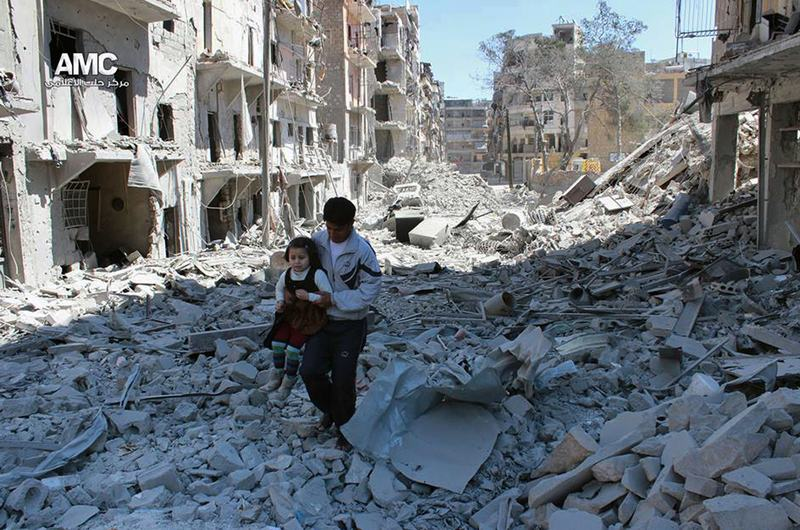 In this April 21, 2014 authenticated file photo provided by the anti-government activist group Aleppo Media Center, shows a Syrian man holding a girl as he stands on rubble in Aleppo, Syria.