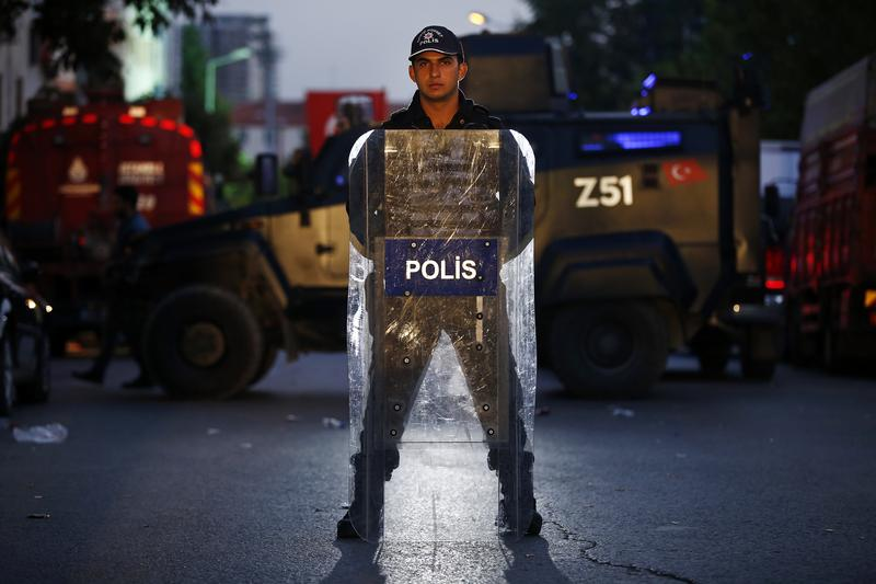 A Turkish police officer stands behind his shield as he secures the scene of a blast in Istanbul, Thursday, Oct. 6, 2016.
