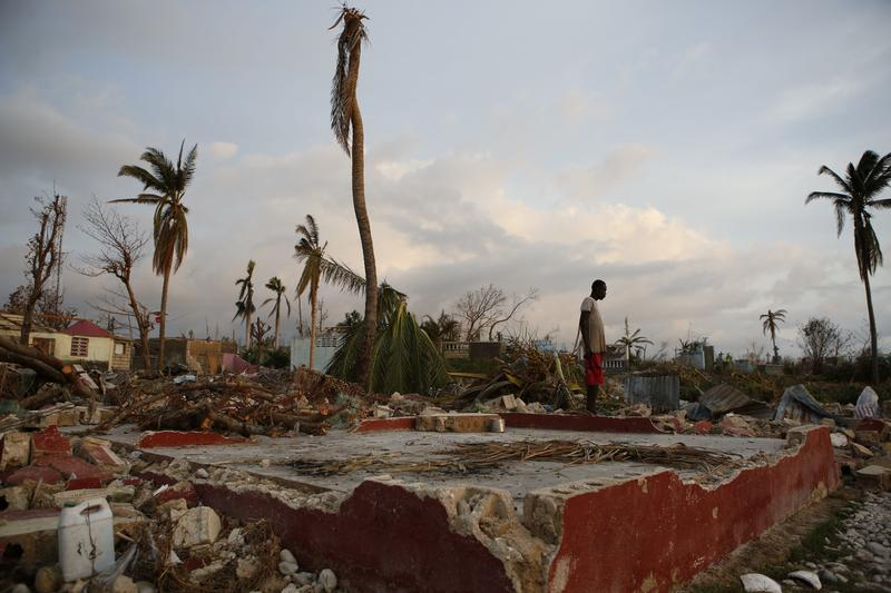 A young man stands next to the foundation of his former house, in a seaside fishing neighborhood almost completely destroyed by Hurricane Matthew in Port Salut, Haiti, Sunday, Oct. 9, 2016.