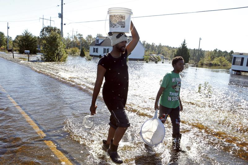 Cedric Blackmon, left, with neighbor Jaywuan McMillian, 13, on a road covered in floodwater associated with Hurricane Matthew on Thursday, Oct. 13, 2016, in Lumberton, N.C.