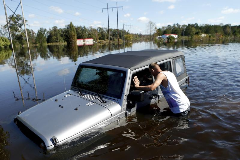 After coming across a Jeep surrounded by floodwaters associated with Hurricane Matthew, Elmer McDonald inspects the inside of a jeep. Oct. 13, 2016, in Lumberton, N.C.