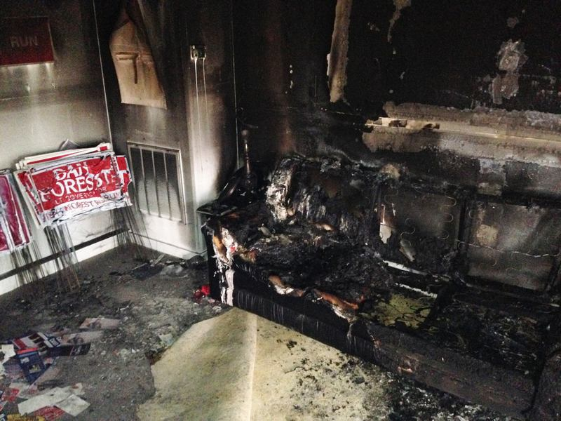 A burned couch is shown next to warped campaign signs at the Orange County Republican Headquarters in Hillsborough, NC on Sunday, Oct. 16 2016.