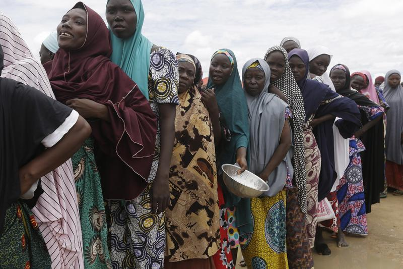 In this file photo taken Saturday, Aug. 27, 2016, women displaced by Islamist extremists wait for food to be handed out to them at the Bakassi camp in Maiduguri, Nigeria.