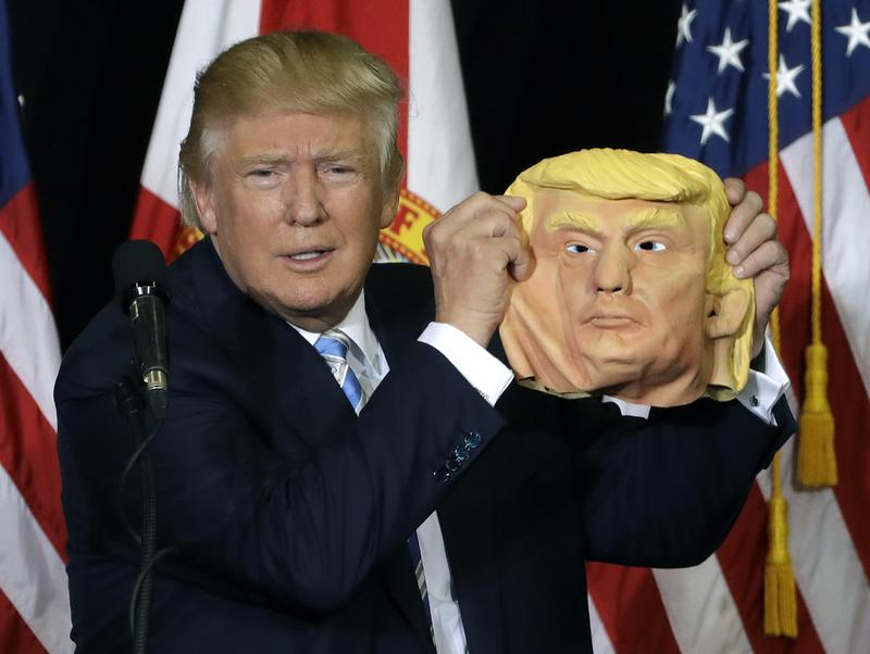 During a campaign speech, Donald Trump holds up a mask of his face in Sarasota, Florida.