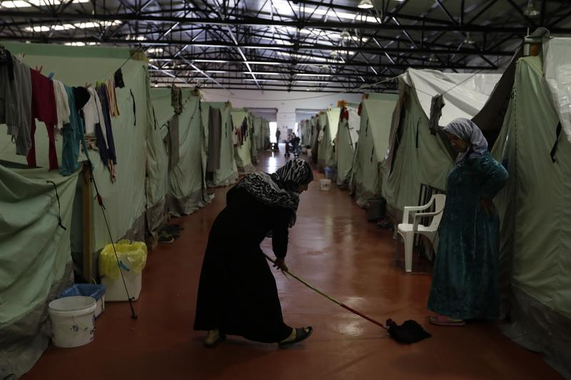 A woman mops the floor outside her tent inside the building of the Kalochori refugee camp, set up in a disused supermarket, on the outskirts of the northern Greek city of Thessaloniki. Nov. 8, 2016