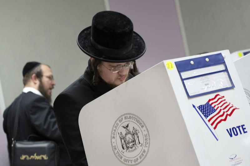 Voters mark their ballots, Tuesday, Nov. 8, 2016, in the Boro Park neighborhood in the Brooklyn borough of New York. The neighborhood has a diverse population, including many orthodox Jews.