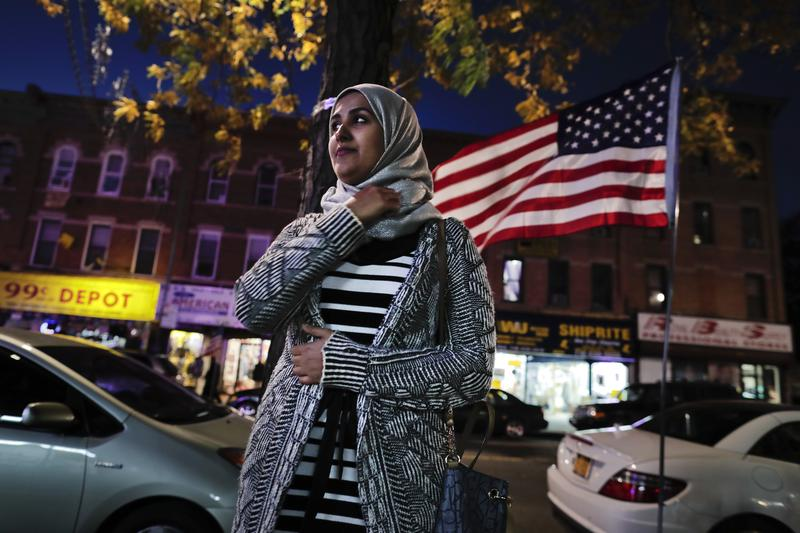 Enas Almadhwahi, an immigration outreach organizer for the Arab American Association of New York, stands for a photo along Fifth Avenue in the Bay Ridge neighborhood of Brooklyn, Friday, Nov. 11, 2016