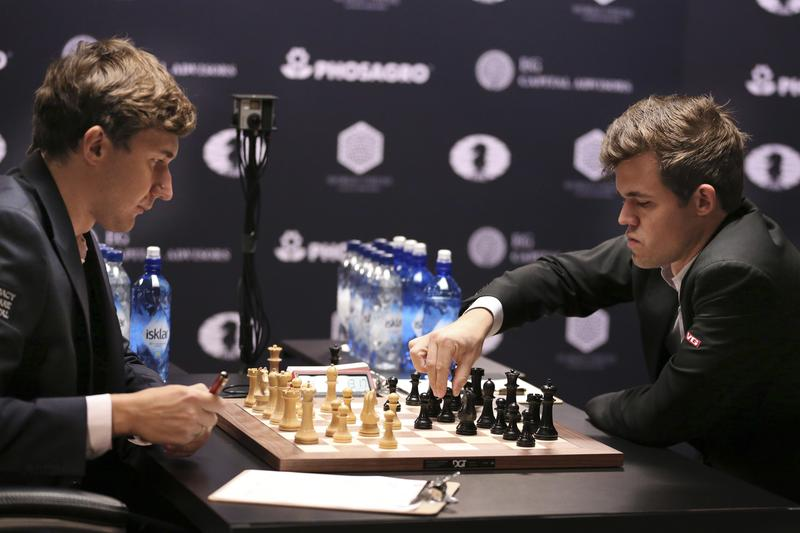 Chess world champion Magnus Carlsen, right, of Norway, makes a move against challenger Sergey Karjakin of Russia, during the fourth round of the World Chess Championship in New York. Nov. 15, 2016