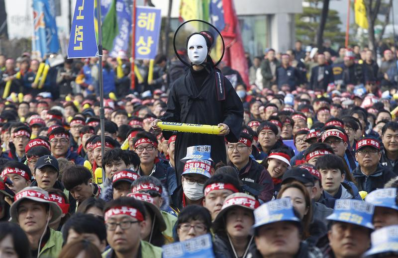 A South Korean protester wearing a mask listens to a speech during a rally calling for South Korean President Park Geun-hye to step down in Seoul, South Korea, Nov. 19, 2016.