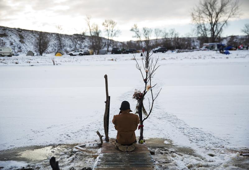 Army veteran Nick Biernacki, of Indiana, prays at the Cannonball River at the Oceti Sakowin camp where people have gathered to protest the Dakota Access oil pipeline in Cannon Ball, N.D. 12/4/16