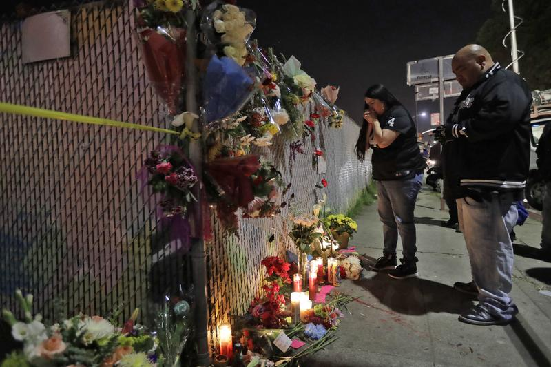 Sol Rodriguez, center, and Aaron Torres visit a shrine for the victims of a warehouse fire near the site Sunday, Dec. 4, 2016, in Oakland, Calif.