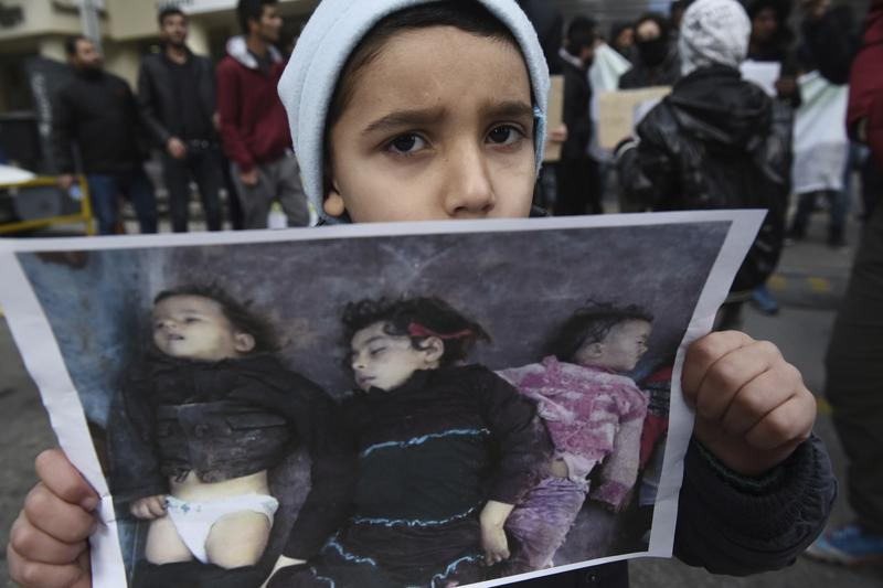 A Syrian boy holds a photo depicting dead children during a protest near the Russian Consulate, at the northern Greek city of Thessaloniki, Wednesday, Dec. 14, 2016.