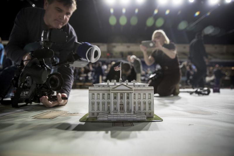 News photographers take photos of a model of the White House during a media tour highlighting inaugural preparations. Dec. 14, 2016