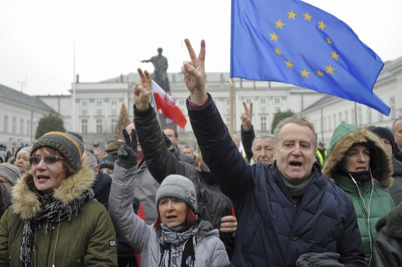 Protesters sing Poland's national anthemn during an anti-government demonstration, in Warsaw, Poland, Saturday, Dec. 17, 2016.