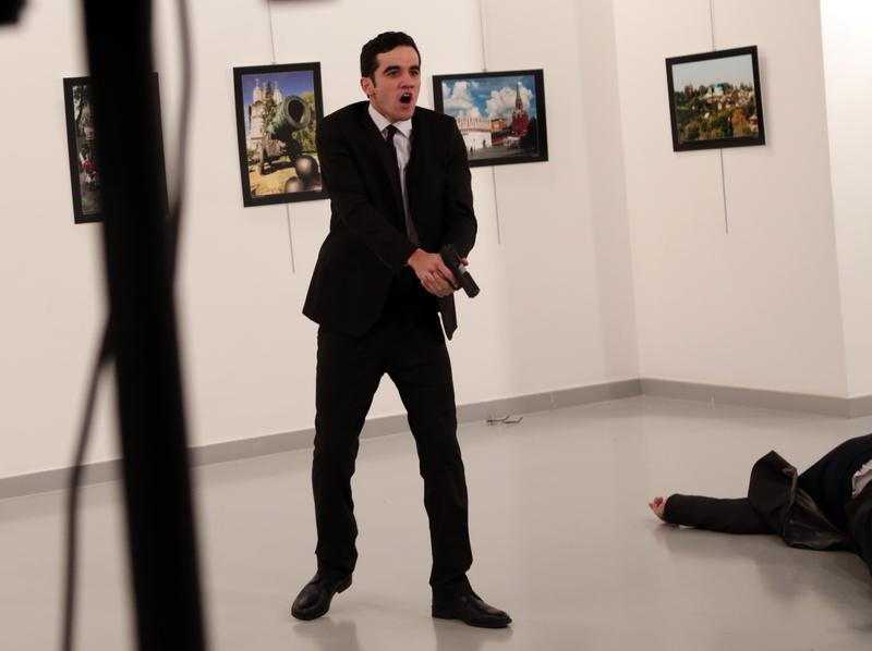 An unnamed gunman shouts after shooting the Russian Ambassador to Turkey, Andrei Karlov, at a photo gallery in Ankara, Turkey, Monday, Dec. 19, 2016.