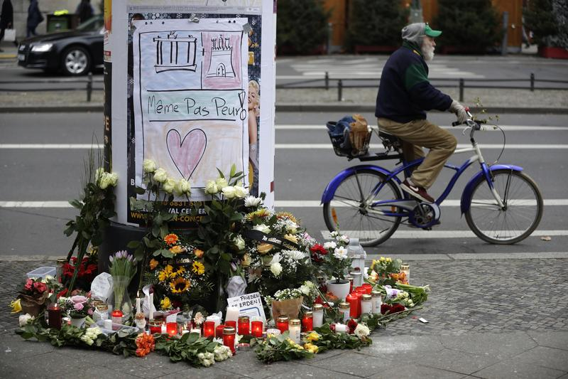 Flowers are seen near the crime scene in Berlin, Germany, Tuesday, Dec. 20, 2016, the day after a truck ran into a crowded Christmas market and killed several people.