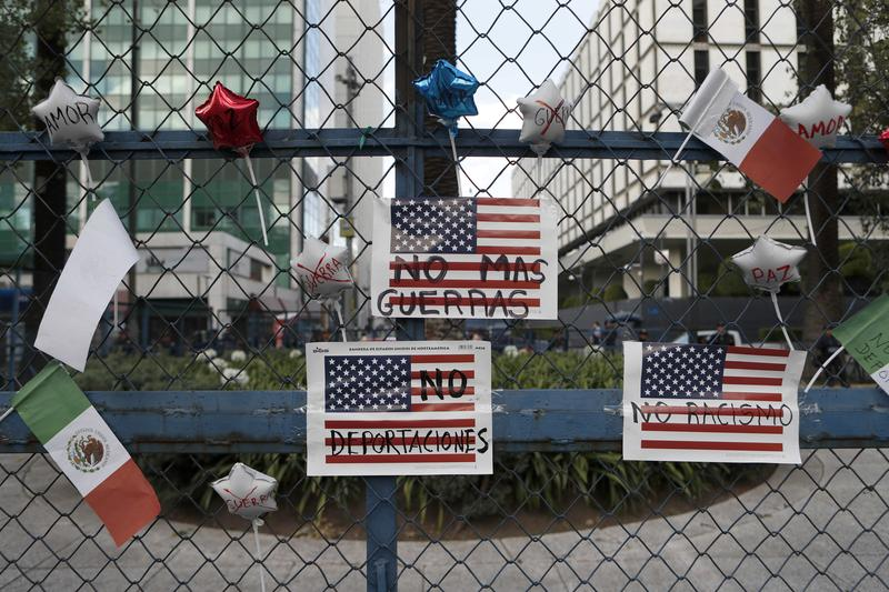 """Signs that read in Spanish """"No more wars,"""" """"No more deportations"""" and """"No racism"""" hang from a fence in front of the U.S Embassy in Mexico City, Jan. 20, 2017."""