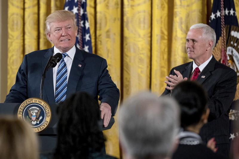 President Donald Trump, accompanied by Vice President Mike Pence, right, pauses while speaking at a White House senior staff swearing in ceremony in the East Room of the White House. Jan. 22, 2017