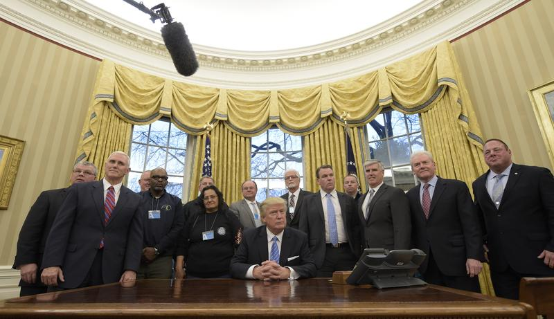 President Donald Trump poses with union leaders in the Oval Office at the White House in Washington, Monday, Jan. 23, 2017.