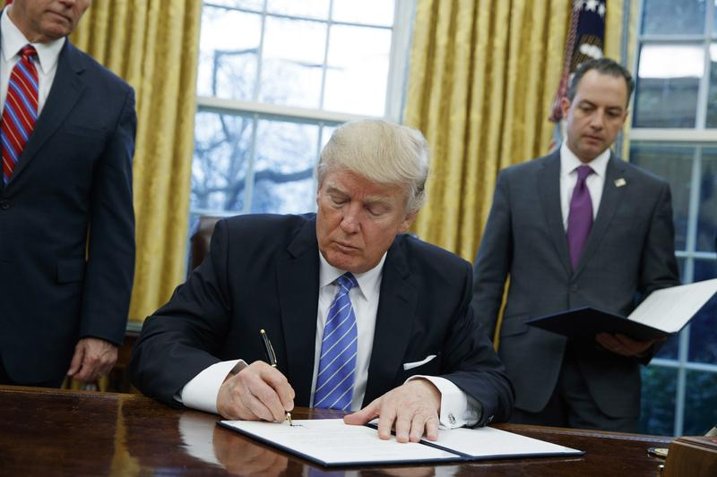 In this Monday, Jan. 23, 2017 photo, President Donald Trump signs an executive order to withdraw the U.S. from the 12-nation Trans-Pacific Partnership.