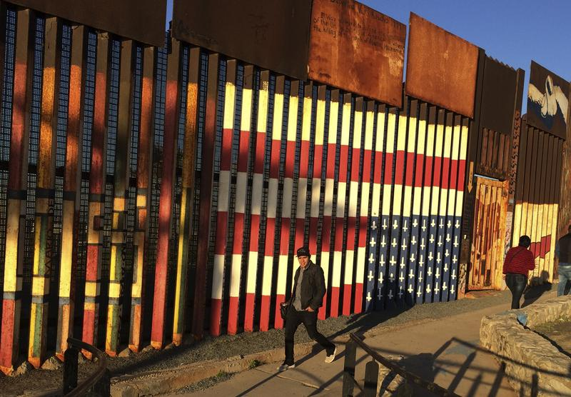 "People walk past a mural painted on a border structure in Tijuana, Mexico, on Wednesday, Jan. 25, 2017. The mural, entitled ""SOS, Deported Veterans,"" was painted in 2013."