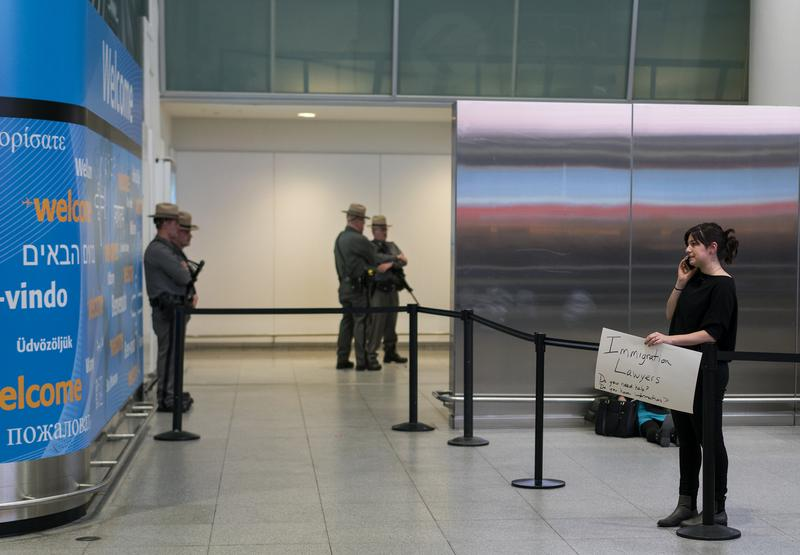 Person holds a sign near an passenger exit point inside Terminal 4 at John F. Kennedy International Airport in New York.
