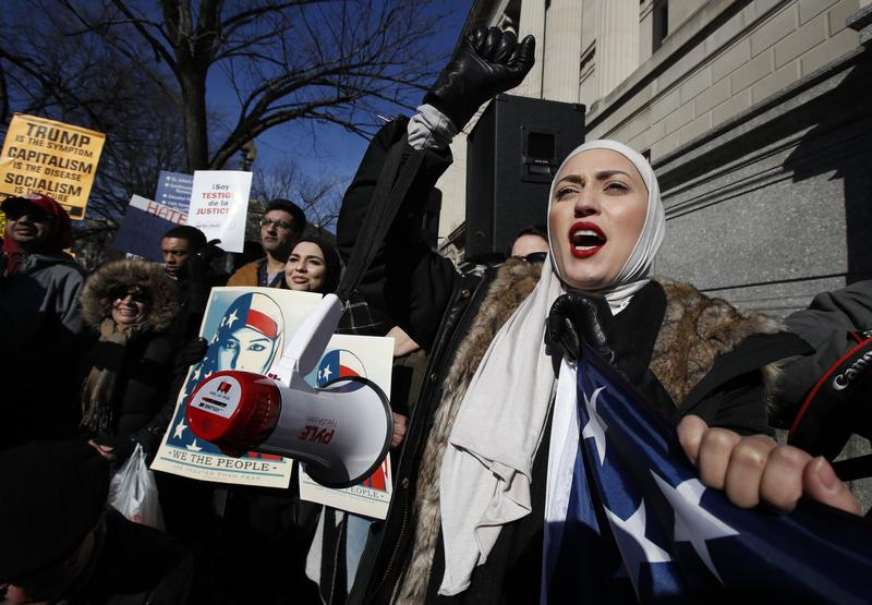 A demonstrator chants during a rally protesting the immigration policies of President Donald Trump, near the White House in Washington, Saturday, Feb. 4, 2017.