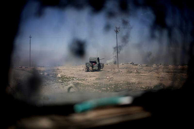 Iraqi police forces fire from a humvee at Islamic State positions from a hillside outside the town of Abu Saif, Monday, Feb. 20, 2017.