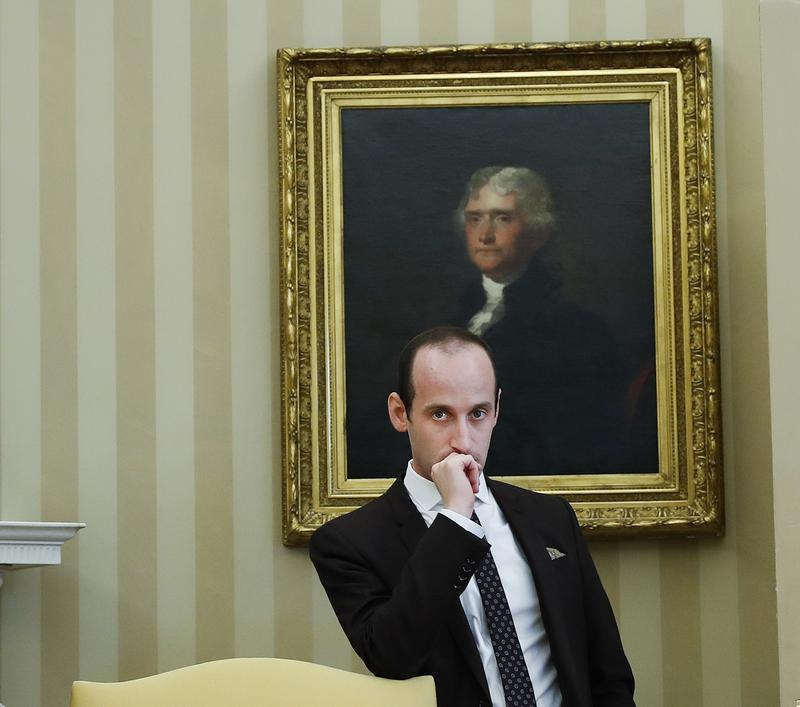 Senior adviser Stephen Miller watches from the back of the Oval Office of the White House in Washington, Friday, Feb. 24, 2017, as President Donald Trump signs an executive order.