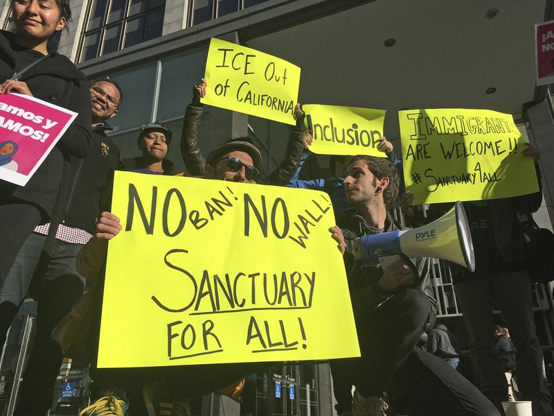 """4/14/17: Protesters hold up signs outside a courthouse where a judge will hear arguments in the first lawsuit challenging President Trump's executive order to withhold funding from """"sanctuary cities."""""""