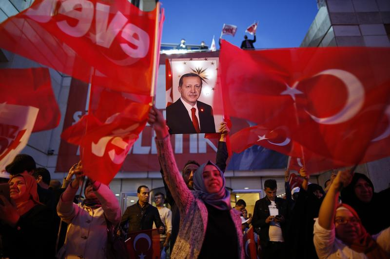 Supporters of Justice and Development party (AK) wave Turkish flags and hold a poster of Turkish President Recep Tayyip Erdogan outside its offices in Istanbul, Sunday, April 16, 2017.