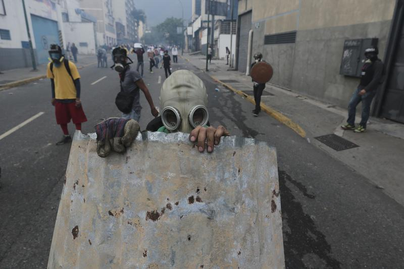 A youth with a gas mask takes cover behind a piece of corrugated tin roofing during anti-government protests in Caracas, Venezuela, Wednesday, April 19, 2017.