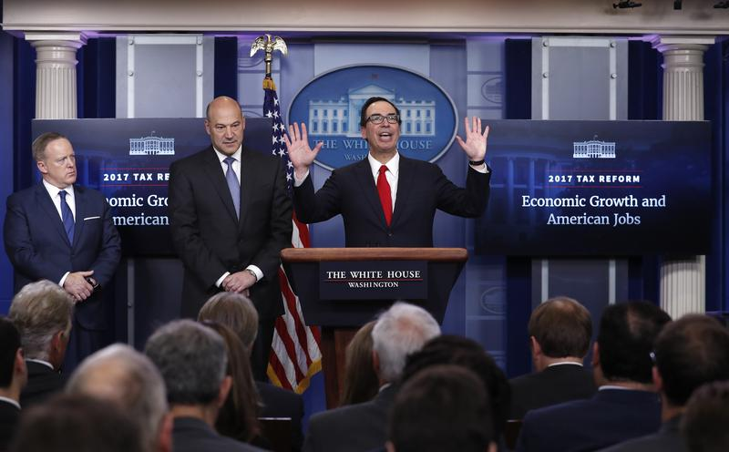 Treasury Secretary Steven Mnuchin, center, joined by National Economic Director Gary Cohn, center,  speaks in the briefing room of the White House in Washington, Wednesday, April 26, 2017.