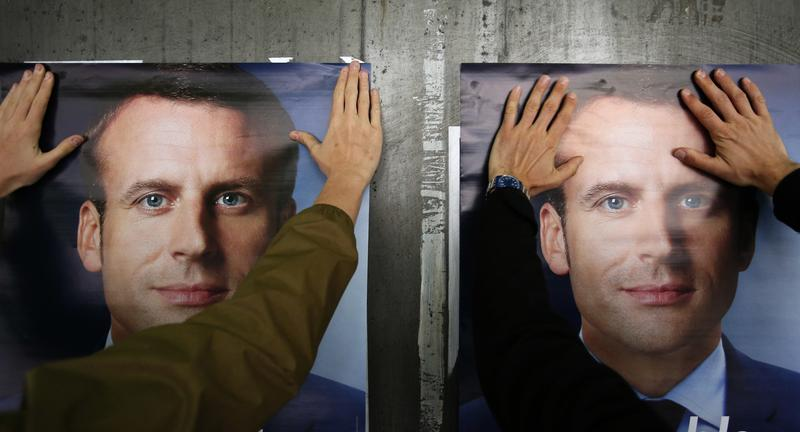 A supporter of French centrist presidential candidate Emmanuel Macron puts up a campaign poster, in Lille, northern France, Tuesday, May 2, 2017.