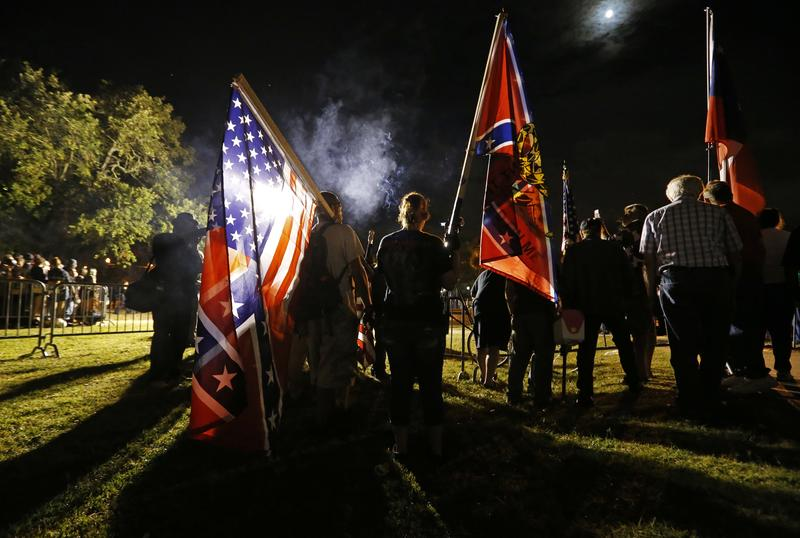 Demonstrators who supports keeping Confederate era monuments hold flags before the Jefferson Davis statue was taken down in New Orleans, Thursday, May 11, 2017.
