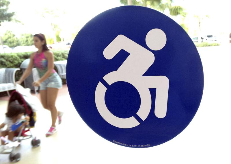 Oct. 7, 2015: A modernized wheelchair sign is affixed to a door at the The Mall at Millenia in Orlando, Fla.