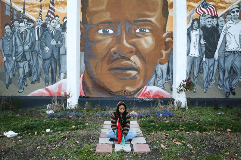 Jazmin Holloway sits below a mural depicting Freddie Gray at the intersection of his arrest, Wednesday, Dec. 16, 2015, in Baltimore.