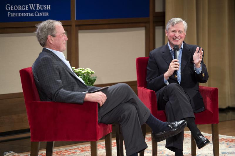 Former President George W. Bush, left, talks with Pulitzer Prize winning author Jon Meacham, right, about Meacham's biography of George H.W. Bush.