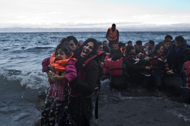 A refugee screams for help after she and her daughter fell into the water after arriving on a dinghy from the Turkish coast to the northeastern Greek island of Lesbos, Friday, Oct. 2 , 2015.
