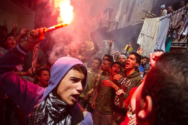 April 24, 2015: An Egyptian youth carries a lit flare as supporters of the Muslim Brotherhood gather in the El-Mataria neighborhood of Cairo, Egypt.